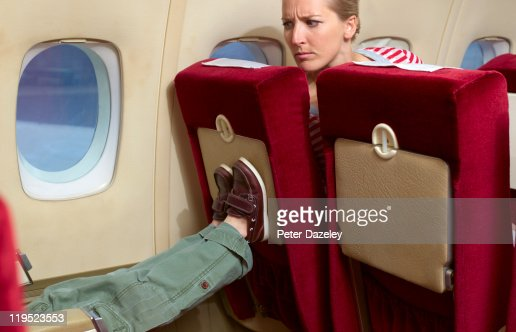 Boy kicking woman's seat on plane : Bildbanksbilder