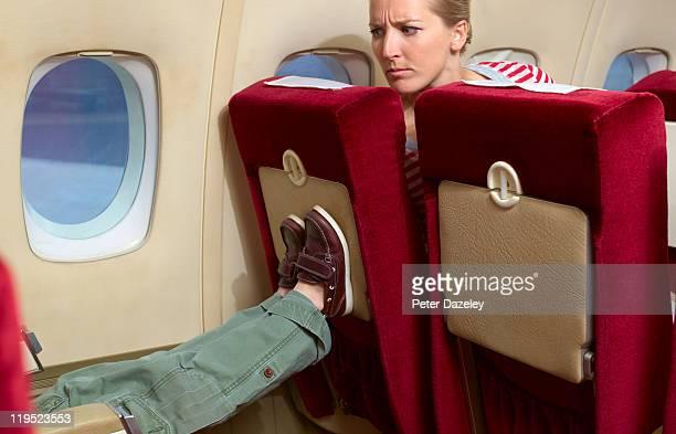Boy kicking woman's seat on plane
