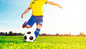 Soccer boy runs towards a ball and is about to kick it hard. The child plays soccer on a football field. It is summer and the sun shines.