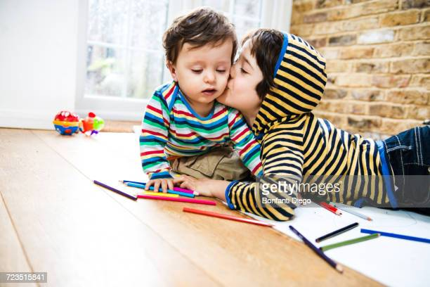 Boy kissing baby brother while lying on floor drawing