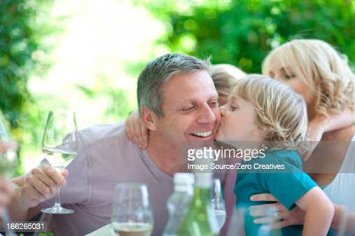 Boy kissing father at table outdoors : Stock Photo