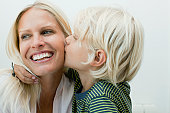 Boy kissing his mother on the cheek