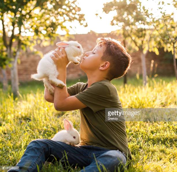 Boy kissing his rabbit