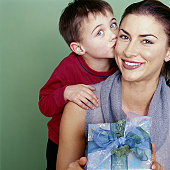 Boy (4-6) kissing mother on cheek, mother holding gift, smiling