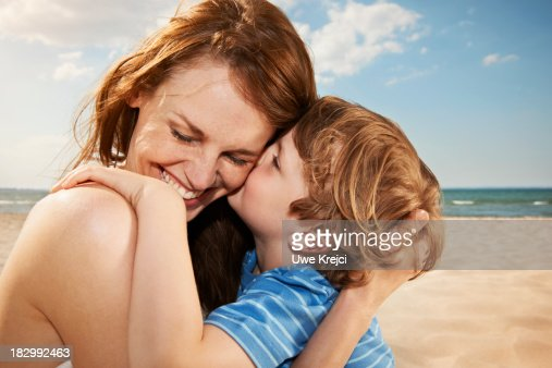 Boy (4-5 years) kissing mother, smiling, close up : Stock Photo