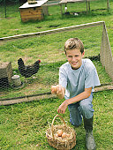 Boy (10-12) kneeling by chicken coop, holding up egg from basket