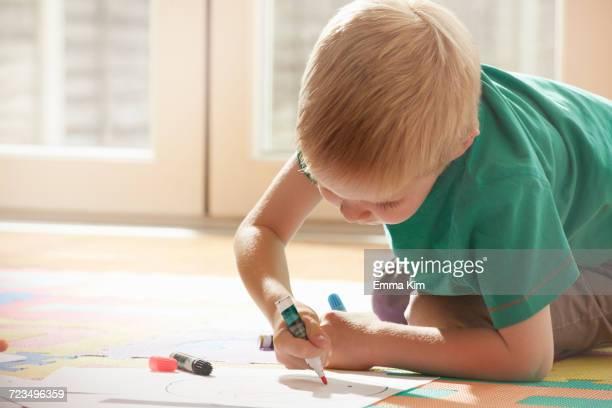 Boy kneeling on floor drawing on paper