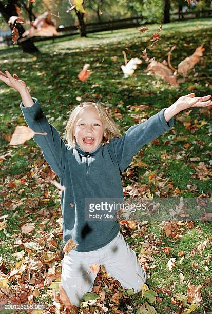Boy (6-8) kneeling on grass throwing fallen leaves in air, outdoors