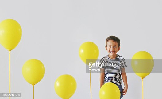Boy (4-5) laughing with yellow balloons