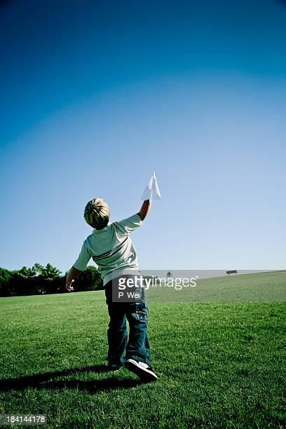 Niño lanzar un avión de papel.