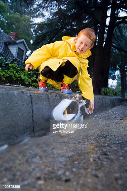 Boy launching homemade boat in gutter after rain