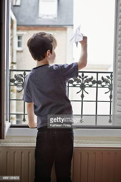 Boy launching paper plane from window