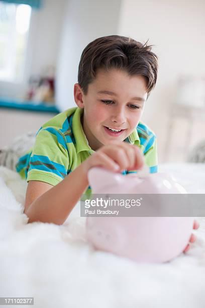 Garçon souvent au lit avec Tirelire en forme de cochon