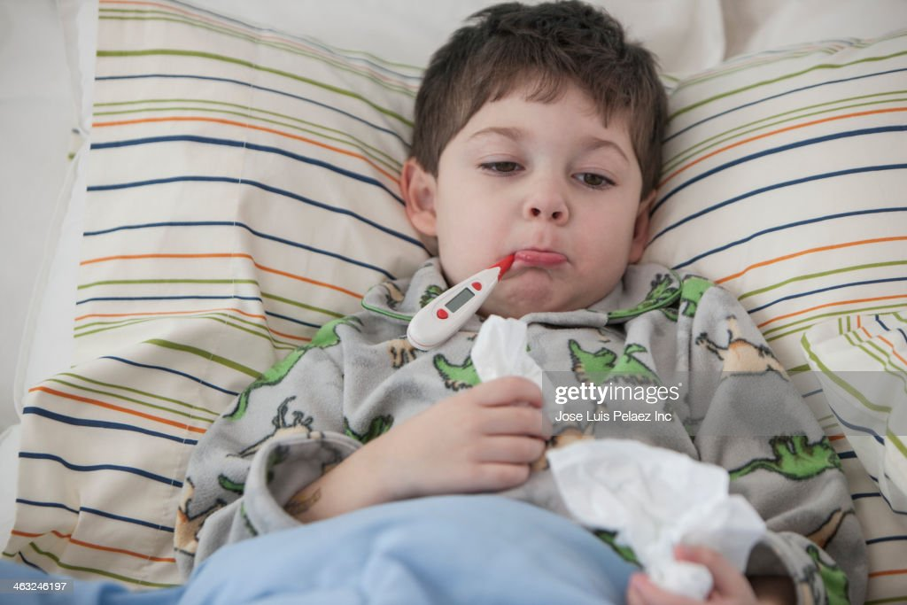 Boy laying in bed with thermometer in mouth