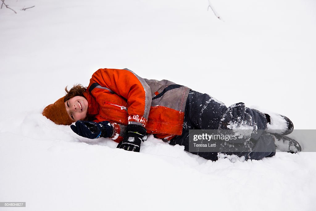 Boy laying in snow smiling