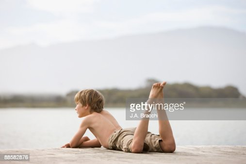 Boy laying on dock near lake : Stock Photo