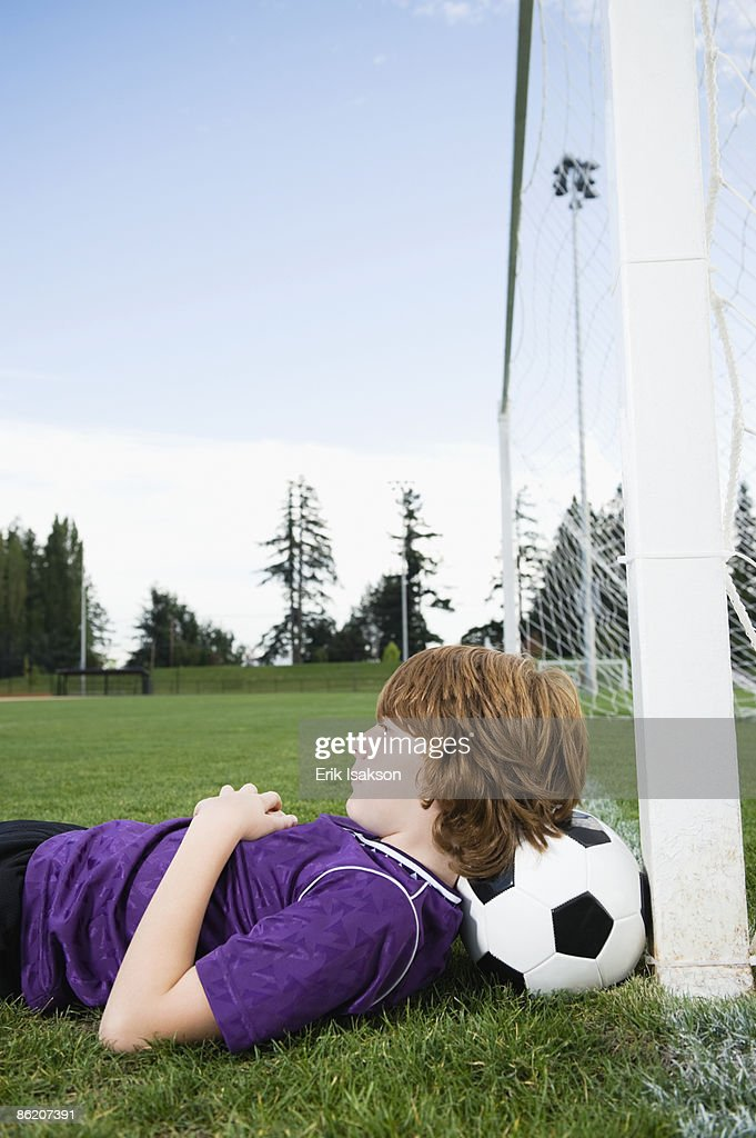 Boy laying on soccer ball against goal : Stock Photo