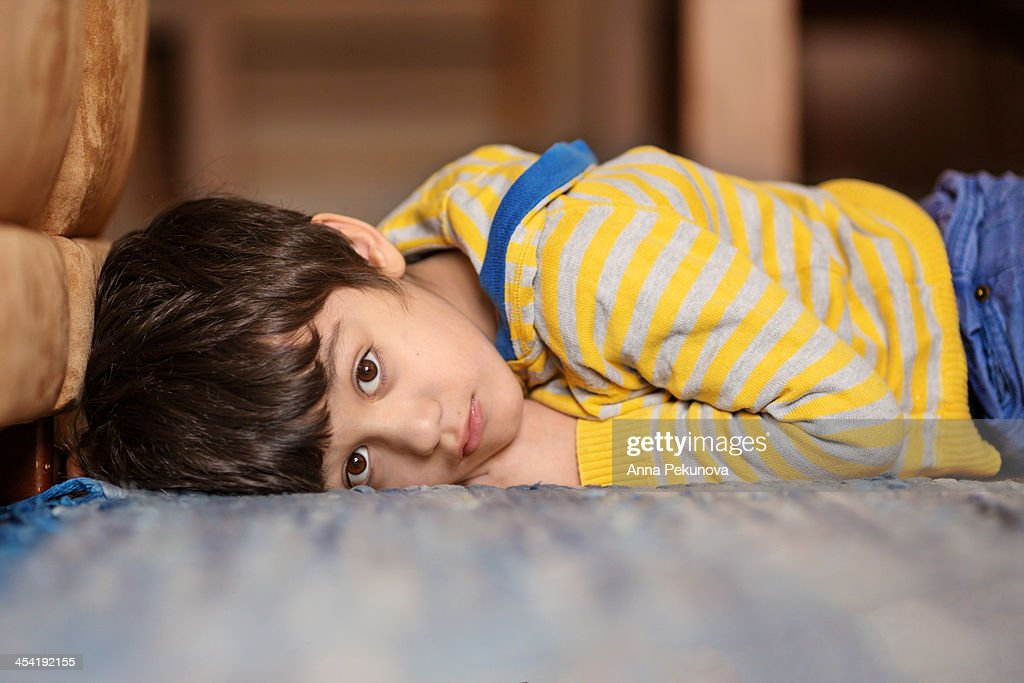 Boy laying on the floor at home : Stock Photo