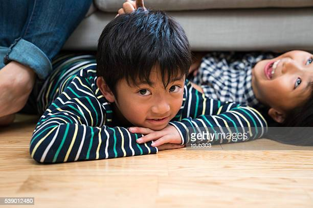 Boy laying on the floor with sister