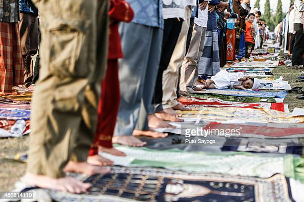A boy lays down during mass pray to celebrate Eidul Fitr on July 28 2014 in Denpasar Bali Indonesia The twoday holiday Eid ulFitr marks the end of...