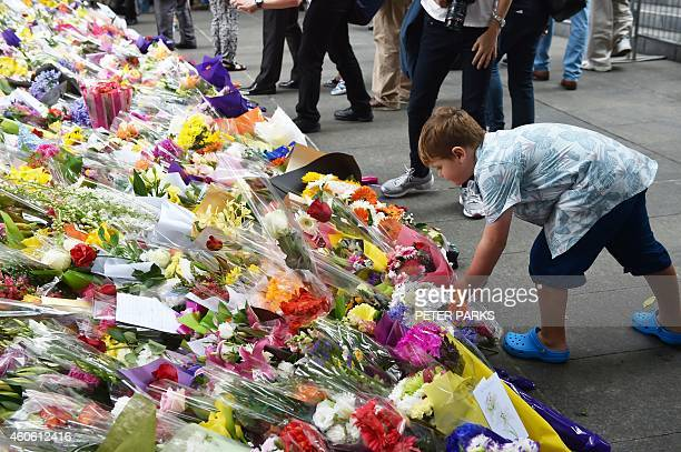A boy lays flowers at a makeshift memorial near the scene of a fatal siege in the heart of Sydney's financial district on December 18 2014 Prime...