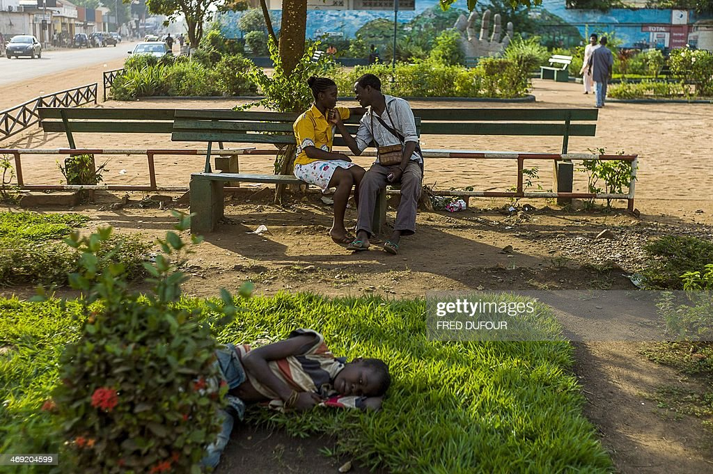 A boy lays on the grass as a couple speaks in a park in the centre of Bangui, Central African Republic, on February 13, 2014, on the eve of Saint Valentine's day, amid an ongoing crisis in the country. The impoverished Christian-majority country descended into chaos in March 2013 after a coup by the mainly-Muslim Seleka rebellion overthrew the government, sparking deadly violence that has uprooted a million people out of a population of 4.6 million.