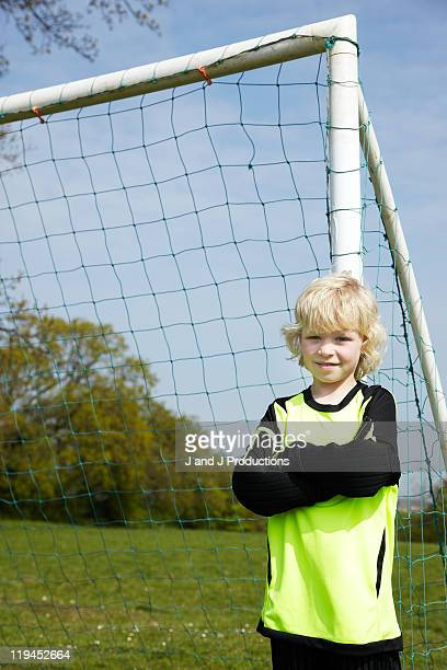 Boy leaning against a goal post