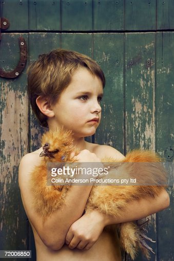 Boy leaning against barn holding chicken : Stock Photo