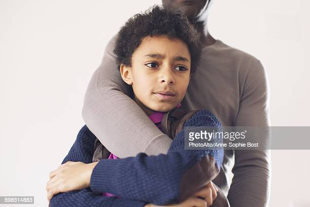 Boy leaning against father with worried expression on face