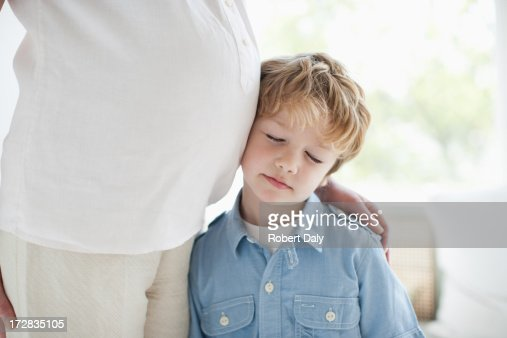 Boy leaning against pregnant mother's stomach