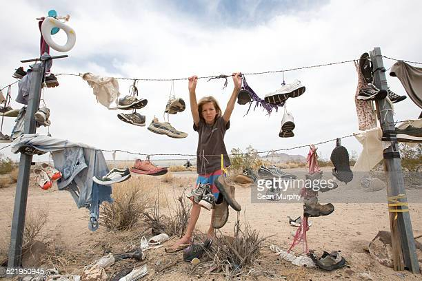 Boy Leaning on Barbed Wire with Hanging Shoes