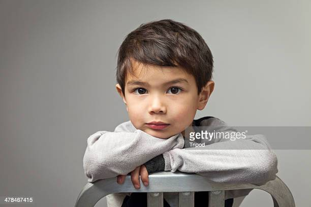 Boy (4-6) leaning on chair, portrait