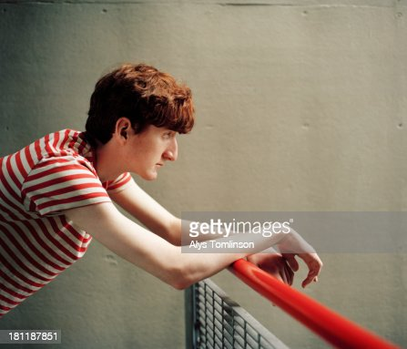 Boy leaning on railing staring into distance : Foto de stock