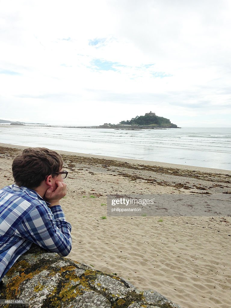 United Kingdom, Cornwall, Marazion, Boy lying on rock and looking at view : Stock Photo