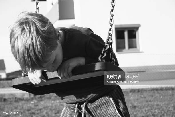 Boy Leaning On Swing At Playground