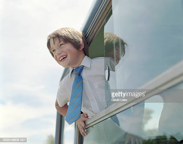 Boy (6-8) leaning out school bus window, smiling