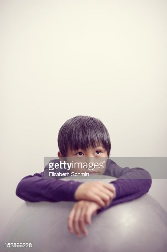 Boy leaning over big white ball : Photo