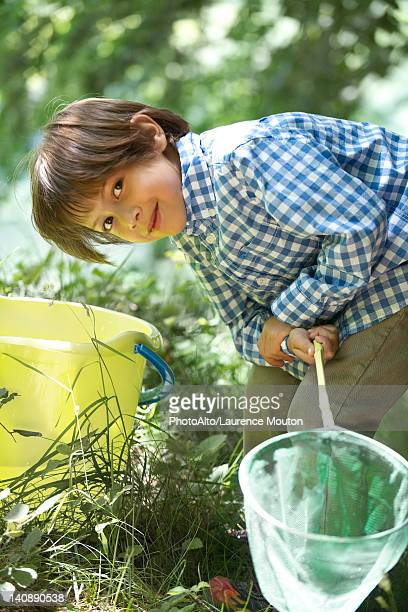 Boy leaning over bucket with fishing net in hands