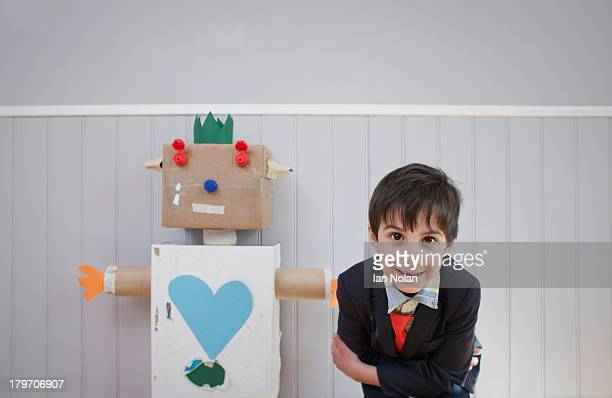 Boy leaning towards camera with homemade toy robot
