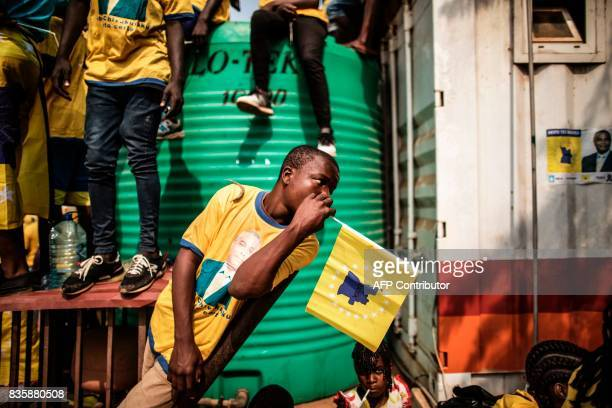 A boy leans on a plank of wood as supporters gather ahead of the address of the leader of the Angolan opposition party CASACE Abel Chivukuvuku durint...