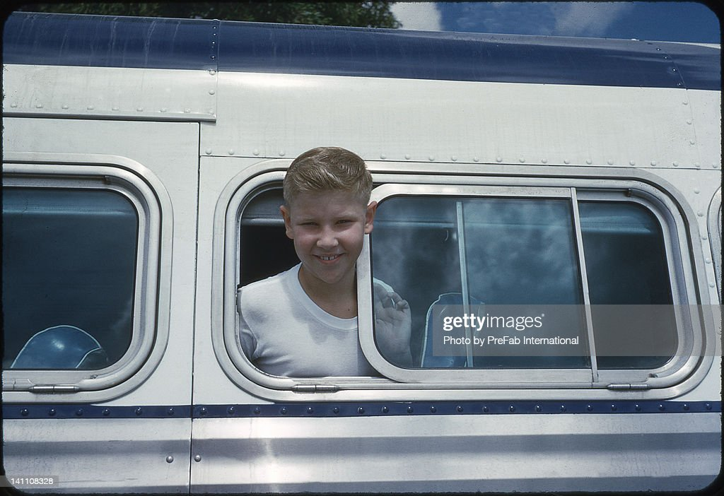 Boy leans out of open bus window : Stock Photo