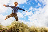 Boy jumping over sand dunes on beach vacation