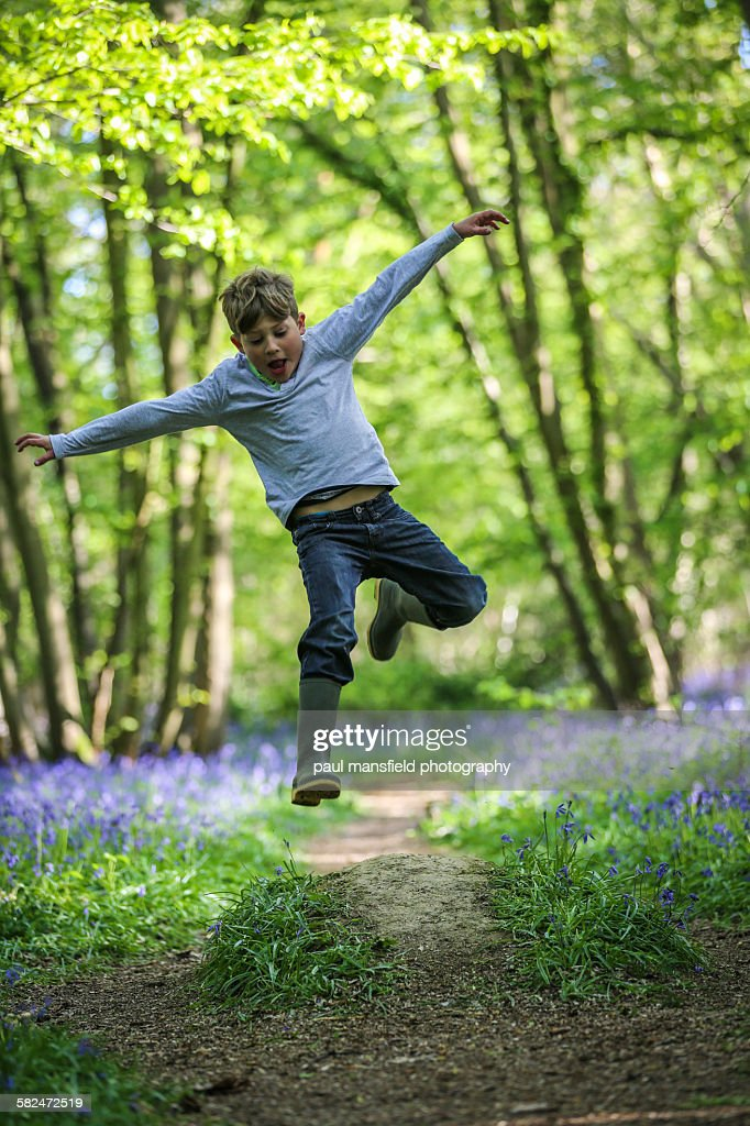 Boy leaping in bluebell wood