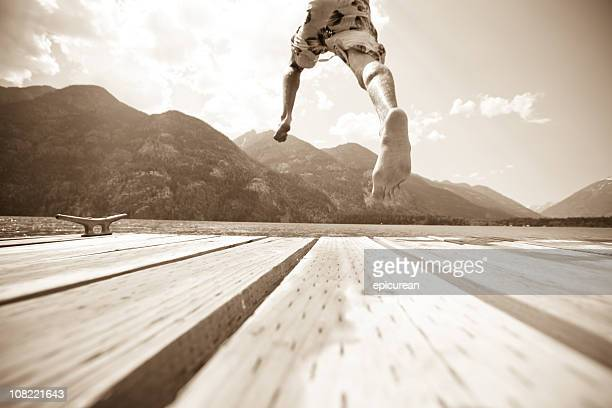 Boy leaping off a dock into cool refreshing water
