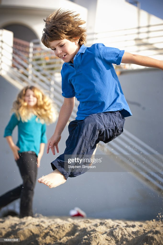 boy leaping off the sand at  the beach : Stock Photo