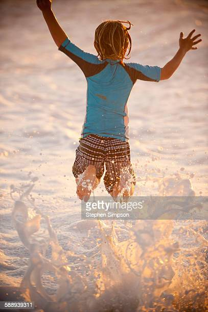 boy leaping over foamy surf