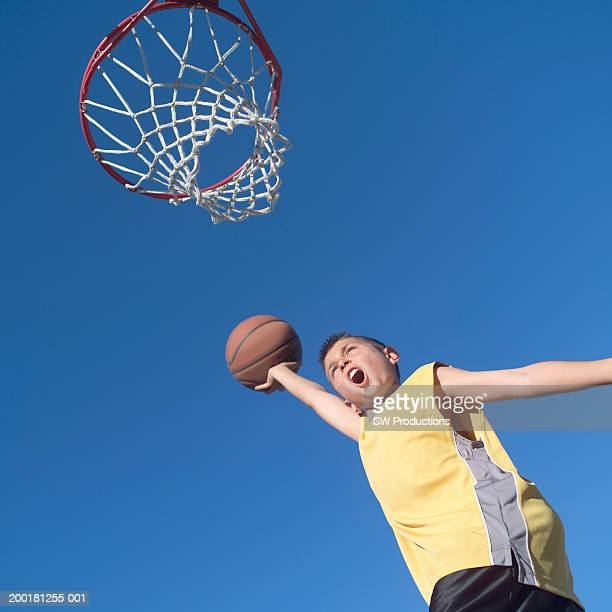 Boy (9-11) leaping to slam dunk basketball, low angle view