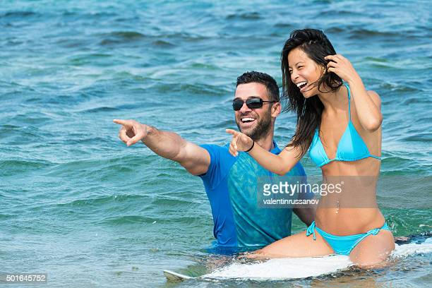 Boy learn beautiful girl to surf