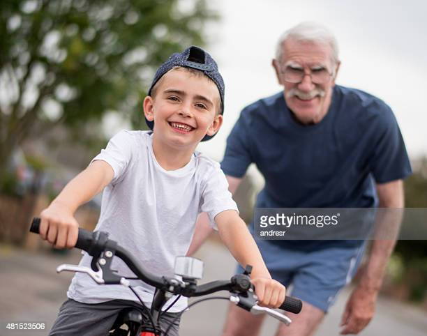 Boy learning how to ride a bike from his grandfather