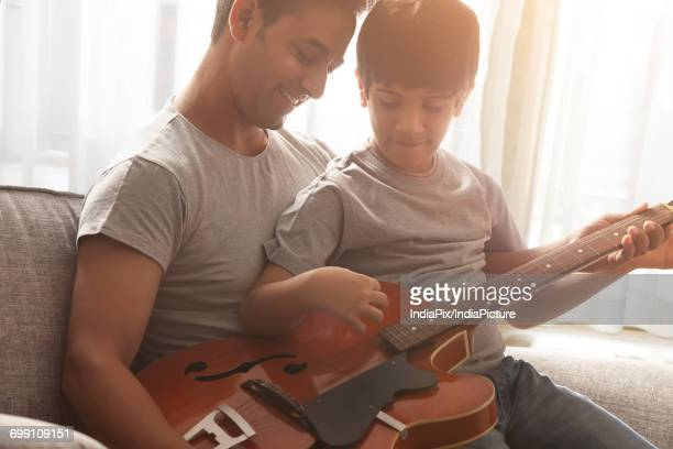 Boy learning to play guitar from his father